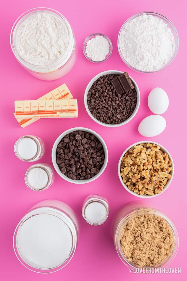 ingredients to make chocolate chip cookies on a pink background