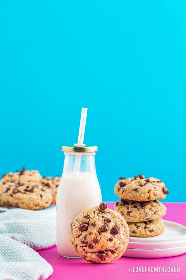 a stack of chocolate chip cookies and bottle of milk