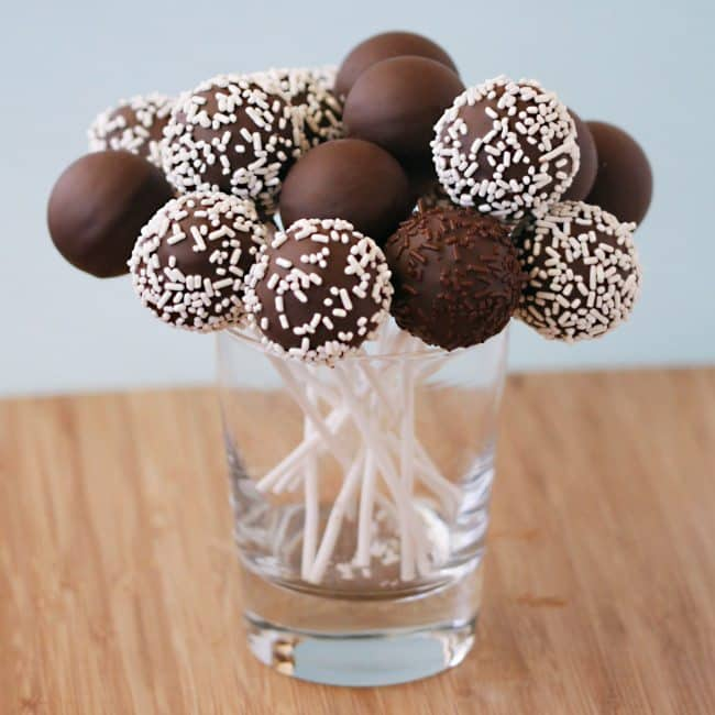 Chocolate cake pops, with white sprinkles, made using a Babycakes Cake Pop Maker, placed into a clear glass cup.