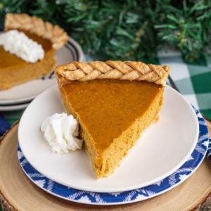 A slice of pumpkin pie on a plate with whipped cream on the side, with a second slice of pie in the background