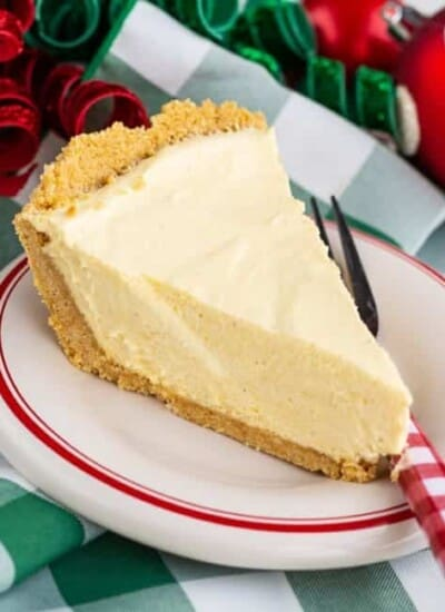 A slice of eggnog pie on a white plate with green and white napkins