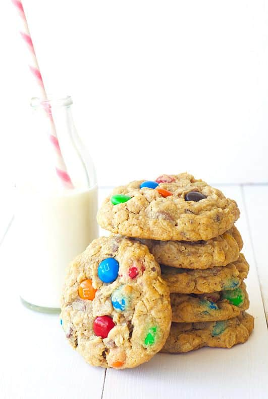 m&m cookies next to a glass of milk