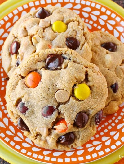 Close up photo of three peanut butter cookies with chocolate chips and Reese's pieces candy in them, sitting on an orange and white plate