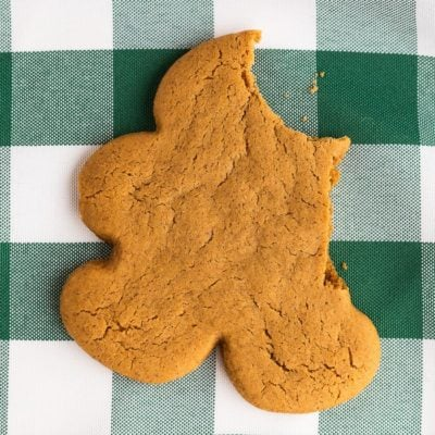 A gingerbread man with a bite taken out on a green and white napkin