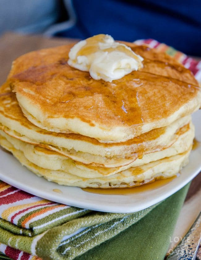 A stack of fluffy pancakes topped with butter and syrup