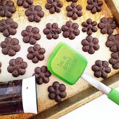 Chocolate spritz cookies on a baking tray with a green spatula