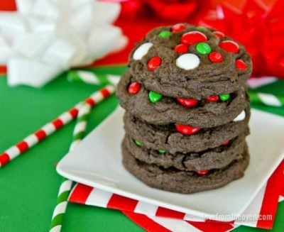 Five Christmas M&M cookies stacked on a white plate