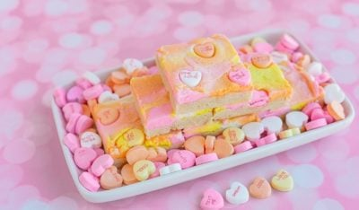 Stack of sugar cookie bars on a tray filled with candy hearts