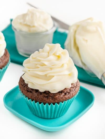 A chocolate cupcake with buttercream frosting on top and a container of buttercream frosting along with a piping bag of frosting sitting behind it