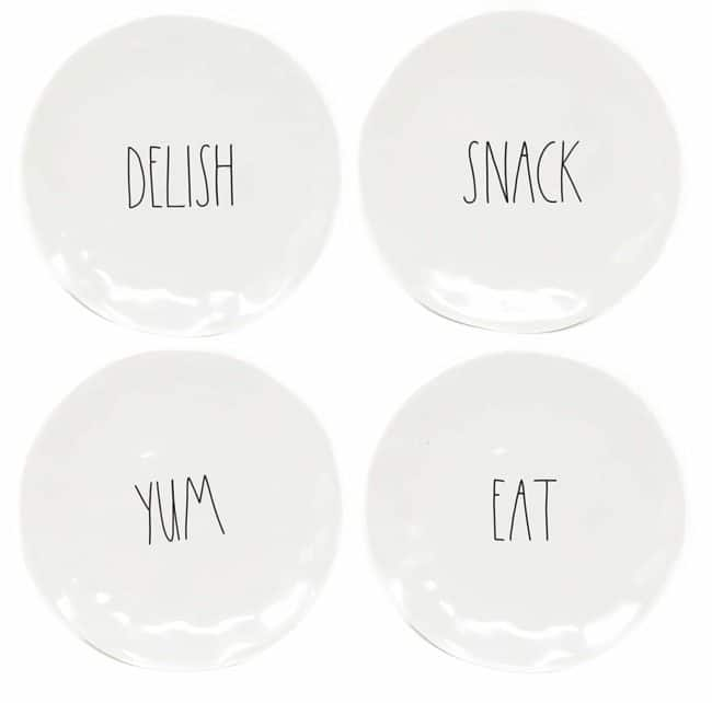 Four Rae Dunn plates with the words delish, snack, yum and eat written on them