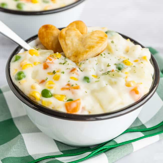 a bowl of pot pie soup with two heart crackers on top