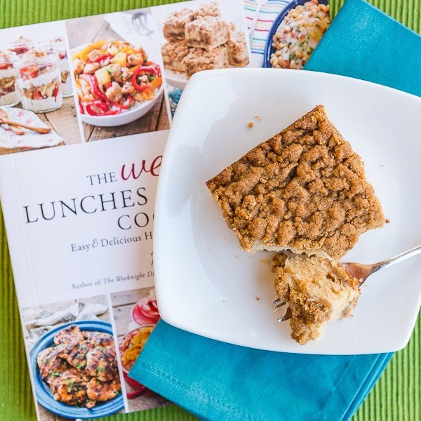 Piece of crumb cake on a plate sitting on a cookbook