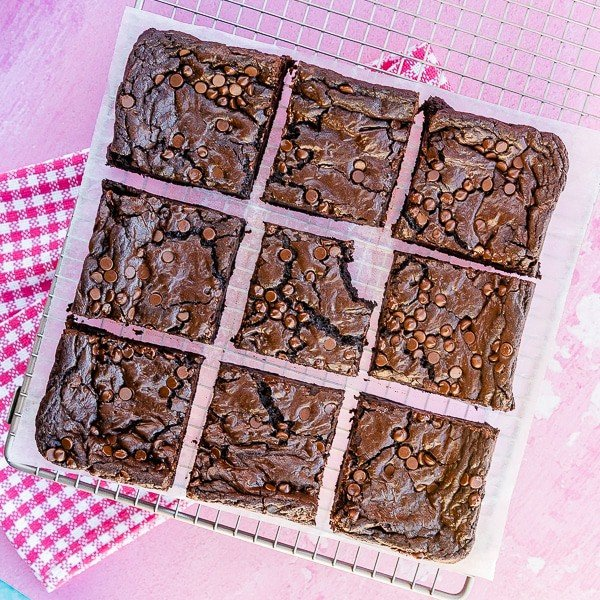 Nine homemade brownies on a cooling tray with a pink background and pink towel