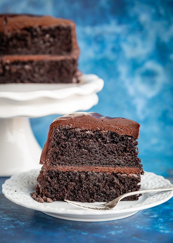 Slice of chocolate cake with half a cake sitting behind it on a cake stand