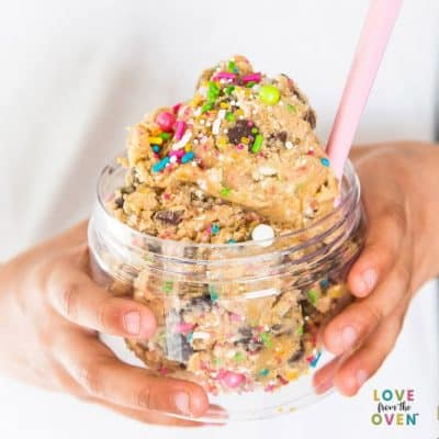 Cookie dough in a clear bowl with sprinkles and a pink spoon