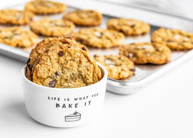 White bowl of crispy chocolate chip cookies in front of a baking sheet of cookies