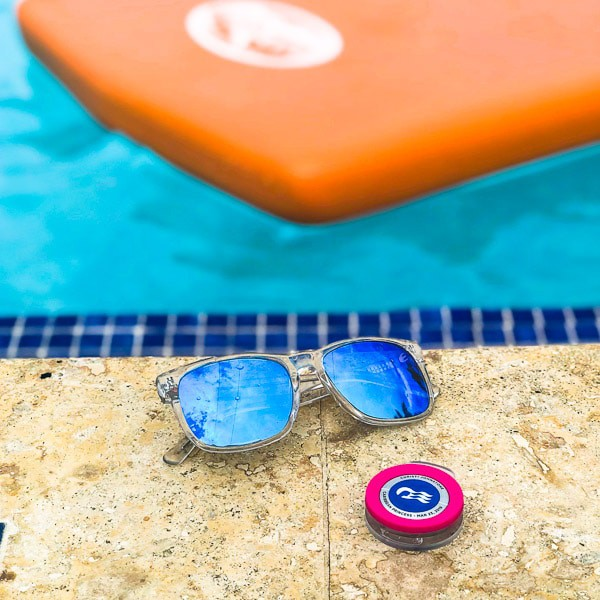Sunglasses and ocean medallion next to a pool with an orange pool float