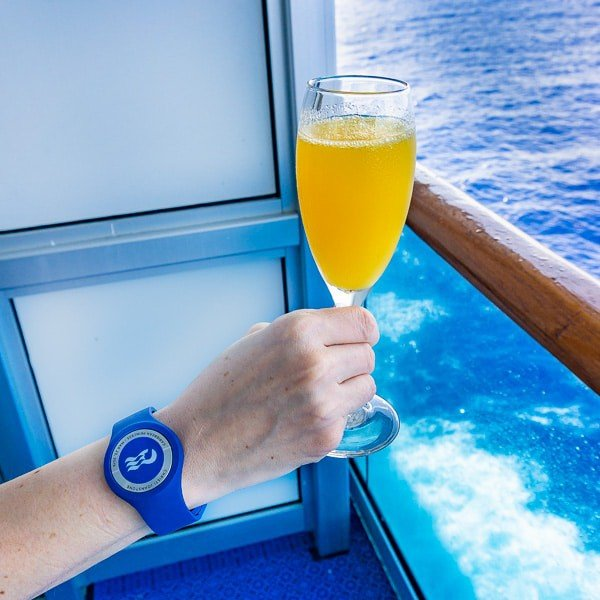 Photo of a hand holding a glass of mimosa while on a cruise ship wearing an ocean medallion