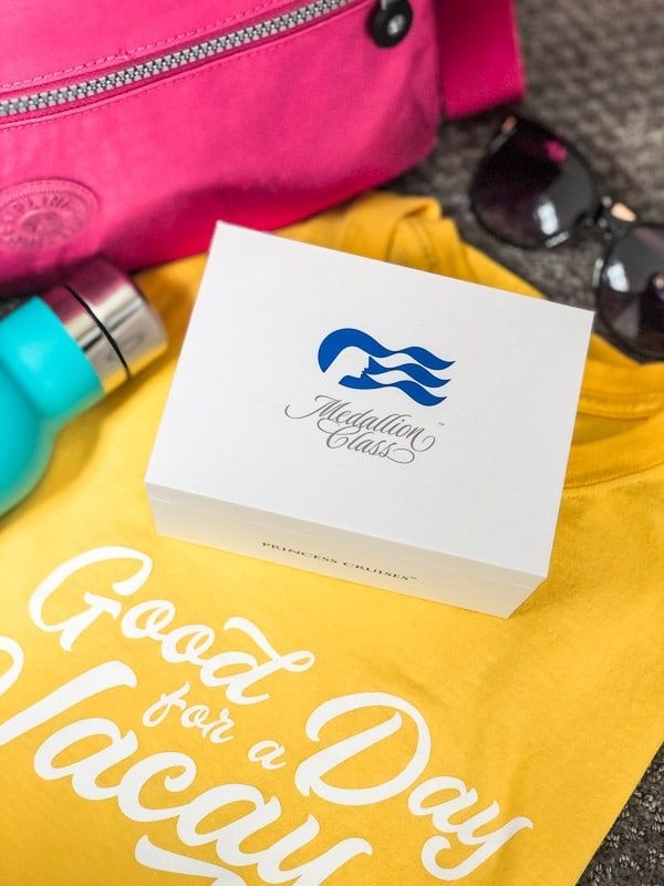 Ocean Medallion box on a yellow shirt next to a pink bag and sunglasses