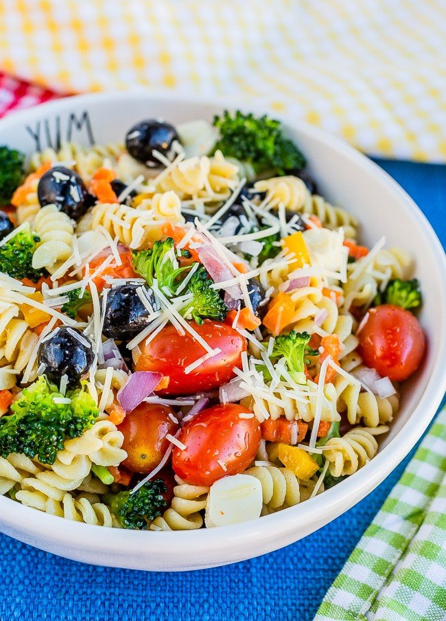 Bowl full of pasta, tomatoes, olives, carrots, broccoli and onions