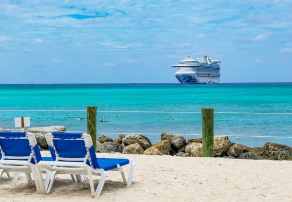 Caribbean Princess cruise ship in turquoise waters as seen from a sandy beach with a blue chaise lounge