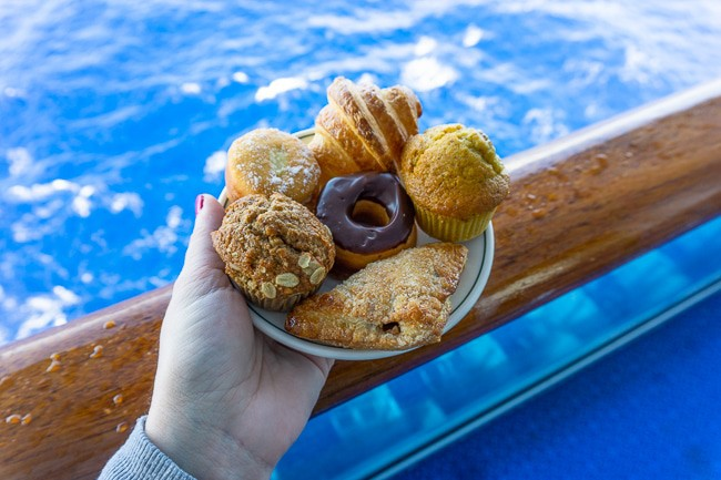 A plate of pastries being held on a blue balcony by blue water on a princess cruise