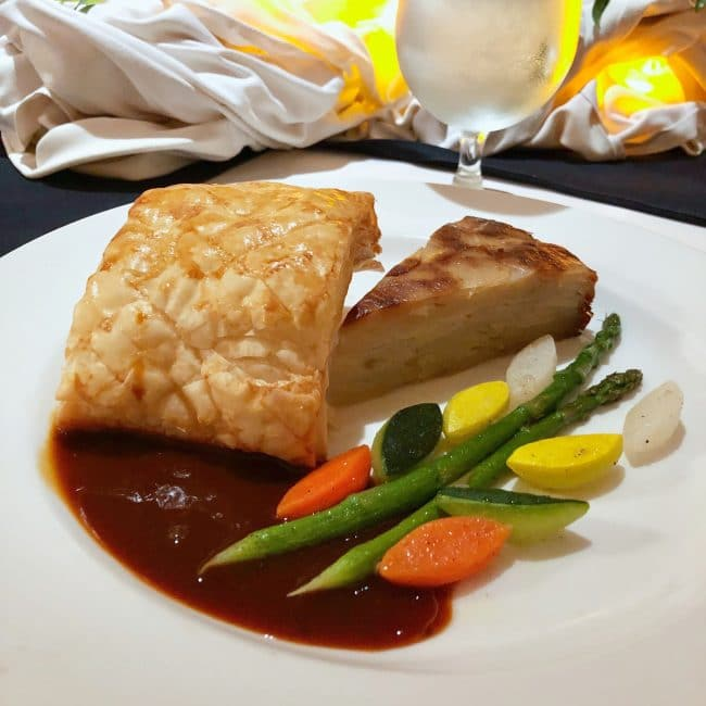 A plate with vegetables and beef wellington at a chef's table dinner on a Princess Cruise