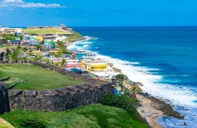 Coast view in Old San Juan Puerto Rico with green mountains, blue water and colorful houses