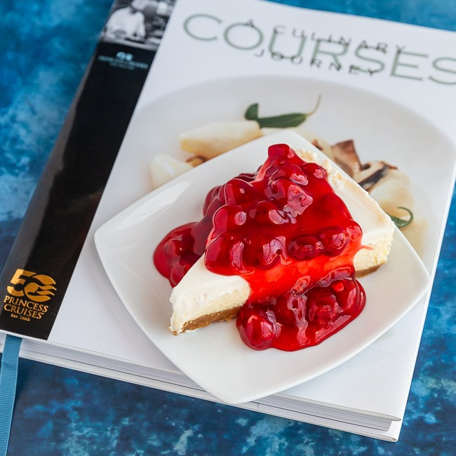 Cheesecake with cherries on top sitting on a cookbook