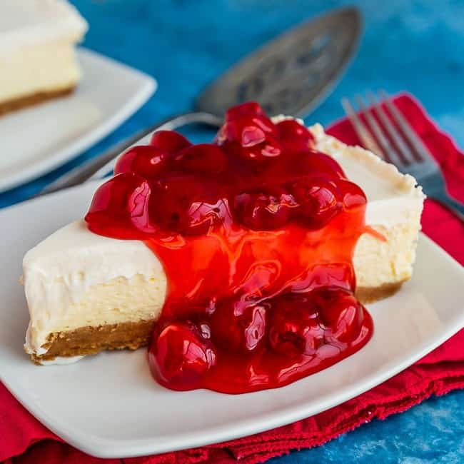 Plate with a slice of classic cheesecake, topped with cherries, sitting on a red napkin with a blue background