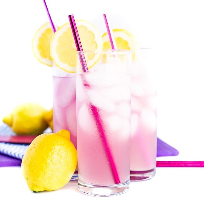 Three pink cocktails with pink straws, lemon slices and a lemon