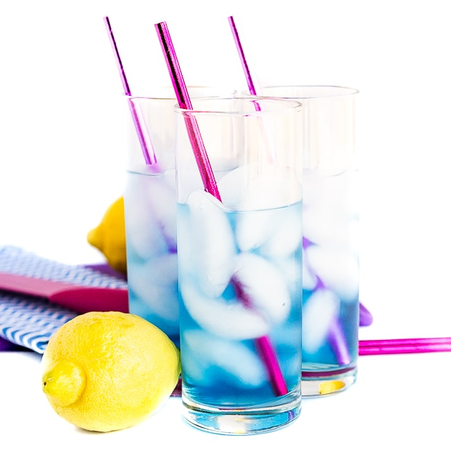 Three blue cocktails with pink straws and lemons