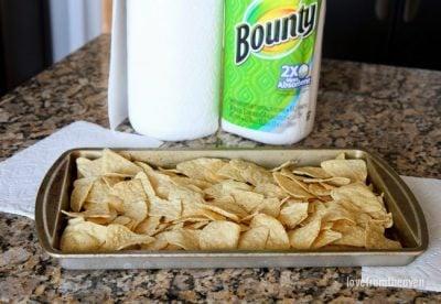Spread tortilla chips onto a baking sheet