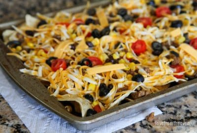 Sheet of uncooked nachos with grated cheese, olives and tomatoes