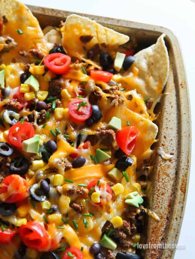 Sheet pan with nachos topped with cheese, tomatoes, ground beef, olives and green onions