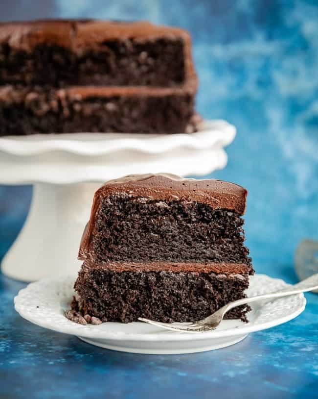 A slice of a two layer Hershey's Chocolate Cake on a white plate with a fork, with the remaining cake behind it on a white cake stand with a blue background