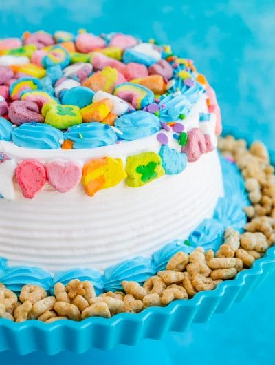 Lucky Charm cake with white and blue frosting, Lucky Charms cereal on the side and Lucky Charms marshmallows on the top