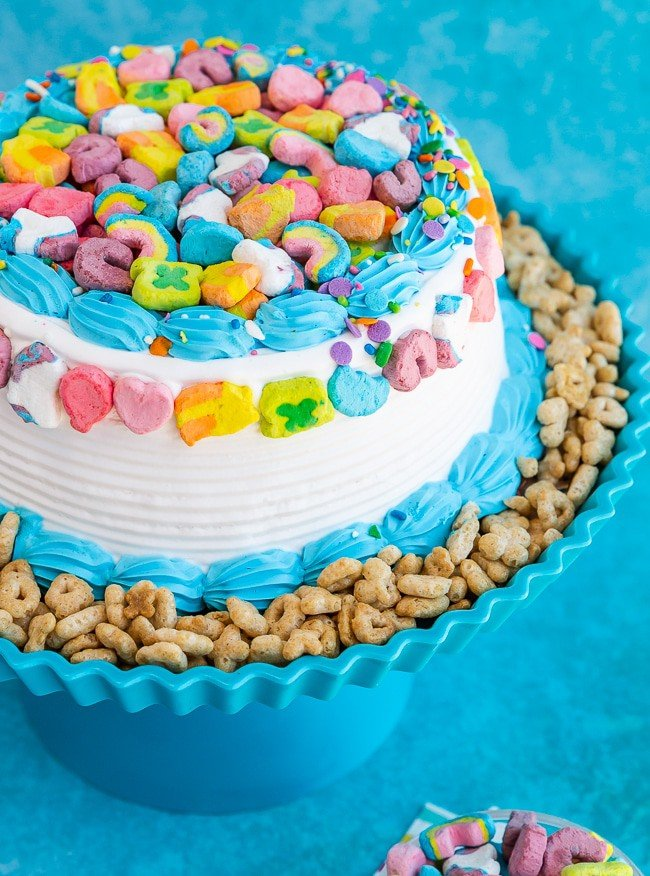 Ice Cream Cake on a blue cake stand with Lucky Charms cereal on the sides and lucky charms marshmallows on the top
