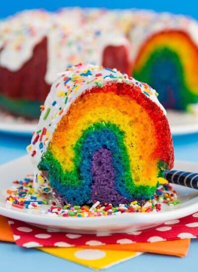 A slice of rainbow bundt cake on a white plate