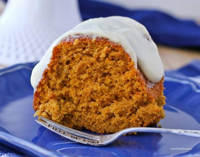 Slice of pumpkin cake with cream cheese frosting on top sitting on a blue plate with a fork