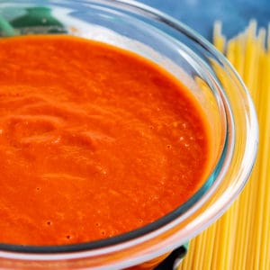 Bowl of San Marzano Tomato Sauce next to pile of uncooked spaghetti noodles