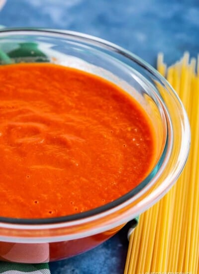 Bowl of San Marzano Tomato Sauce next to pile of uncooked spaghetti noodles