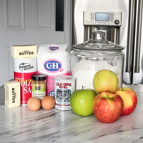 Ingredients needed to make apple cobbler on a countertop, including apples, flour, sugar, butter, eggs, cinnamon, baking power