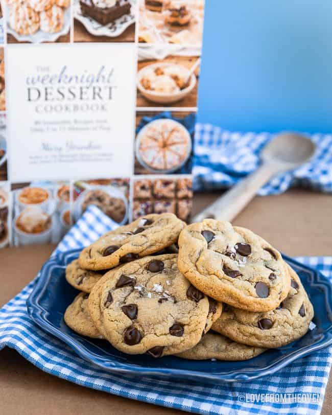 A blue plate of chocolate chip pudding cookies in front of The Weeknight Dessert Cookbook
