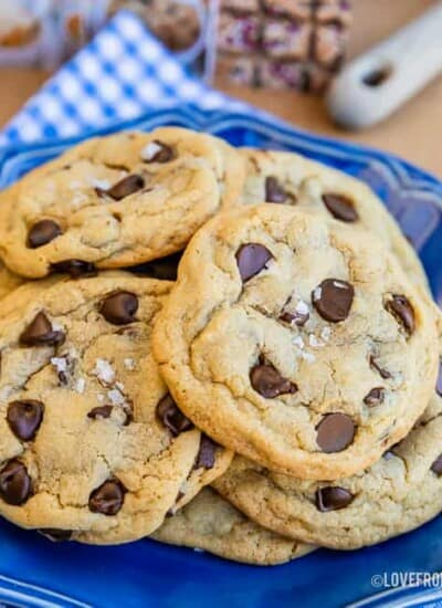 Chocolate chip pudding cookies with sea salt flakes on top, sitting on a blue plate with a blue and white napkin underneath