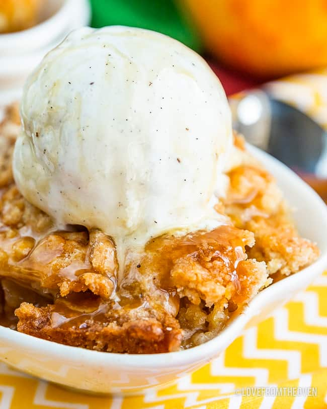 Bowl of easy apple cobbler with vanilla ice cream on top, sitting on a yellow and white napkin