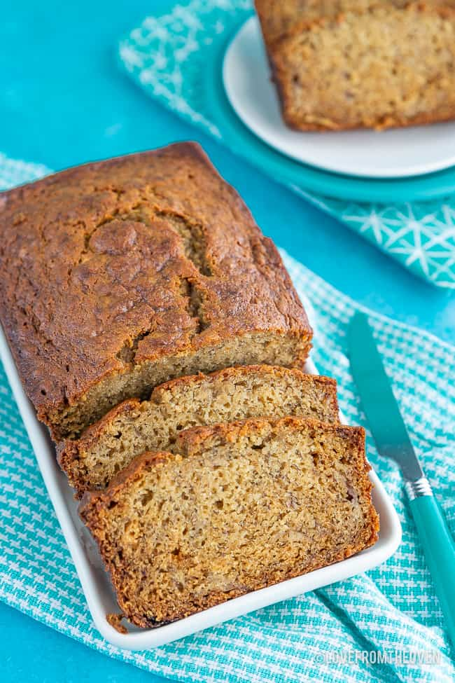 Loaf of banana bread with two slices cut out, sitting on a blue background with a blue check napkin