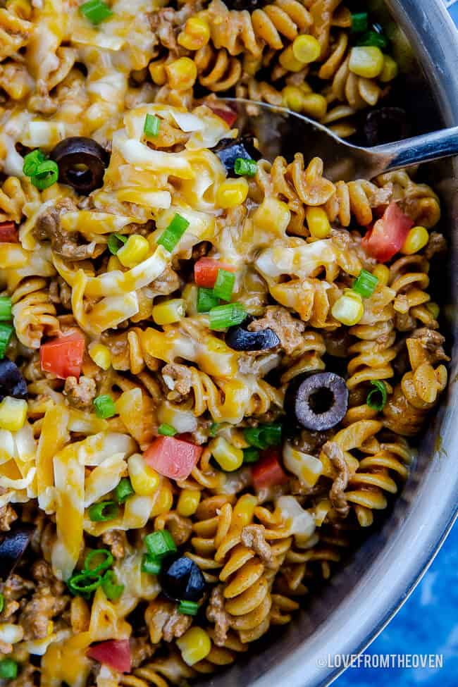 A blue bowl filled with pasta and vegetables