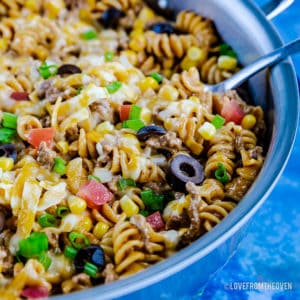 A blue bowl filled with pasta and vegetables,