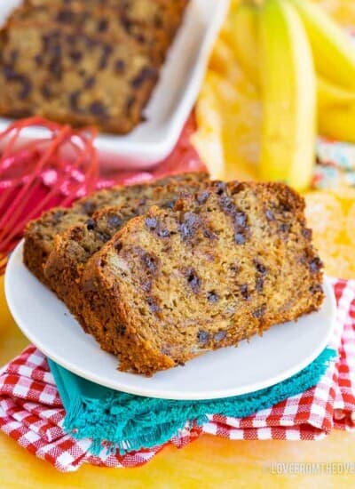 Two slices of chocolate chip banana bread, on a white plate, with blue, read and yellow napkins. More slices of banana bread, and bananas, in background.